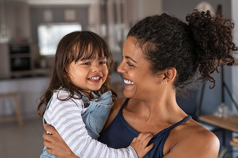 Healthy mom holding child and smiling
